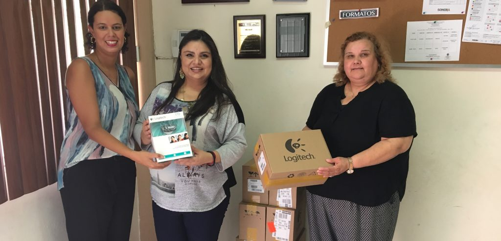 Fernanda hands off boxes of webcams to teachers at school so they can send and receive video messages with their partner students in their Level Up Village courses.